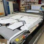 Machine de découpe de tissu dans un atelier textile français